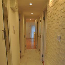 廊下の「タイル」貼り、壁面の「エコカラット」が印象的。玄関収納はトール型タイプで収納力があります(玄関)